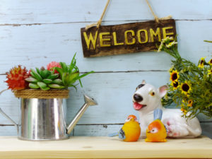 Welcome sign with flowers and a toy dog that looks a lot like the author's little white dog.