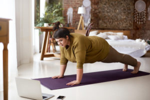 Attractive barefoot young overweight female doing plank on yoga mat while training indoors, watching online video via laptop. Sports, well being, technology and active healthy lifestyle concept