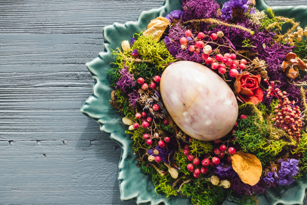 Purple Stone Egg Nestled with Dried Botanicals on Turquoise Plate