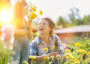 women and child smiling in garden. Connotes growth.