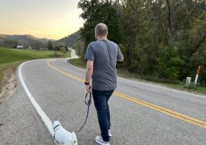 A man and his little white dog walking down a road that winds through the valley ahead of him.